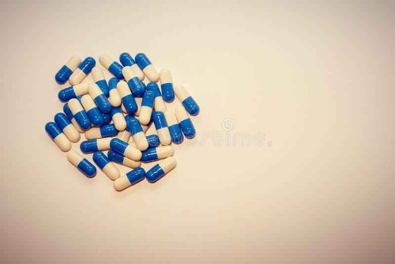 Une poignée de pilules Médicaments de capsules blancs et médicament bleu photos stock