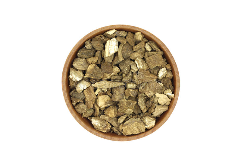Une poignée de racine sèche de bardane dans un plat en bois images stock