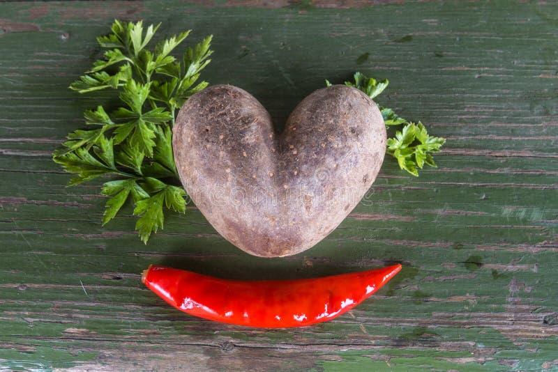 Une pomme de terre et un poivre - un coeur et un sourire photos libres de droits