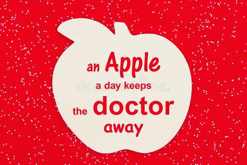 Une pomme par jour empêche le médecin de transmettre son message avec une pomme de bois image libre de droits