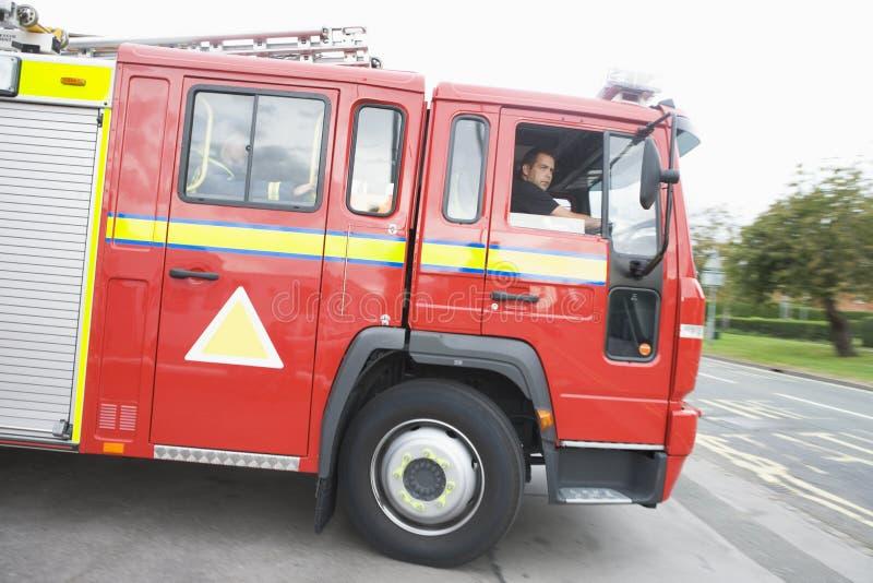 Une pompe à incendie partant de la caserne de pompiers images stock