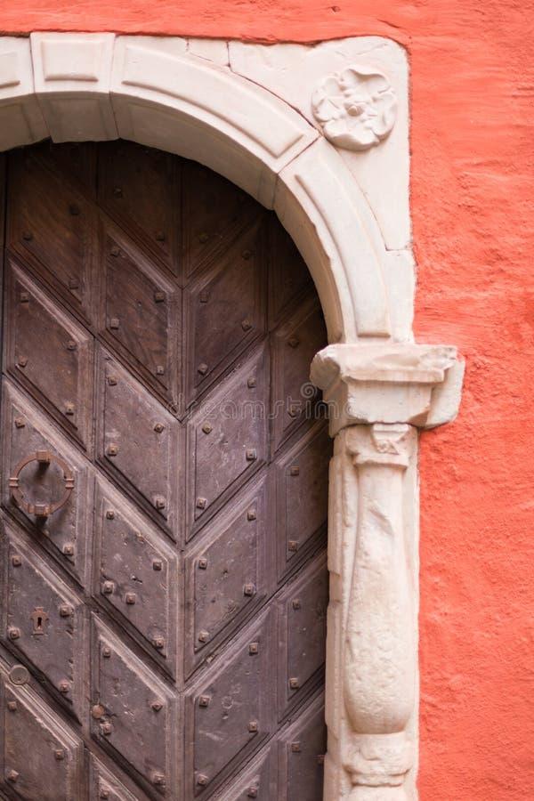 Une porte en bois antique dans l'arcade contre le contexte d'un mur de terre cuite image libre de droits