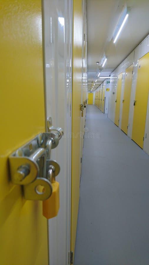 Une porte jaune à l'extrémité d'un couloir d'unité de stockage image stock
