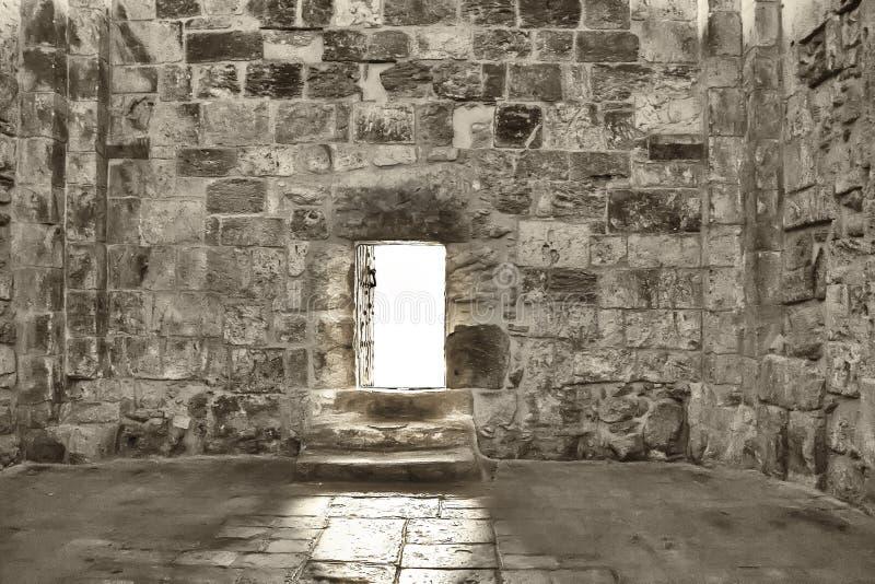 Une porte ouverte dans laquelle la lumière du soleil lumineuse tombe dans un vieux mur en pierre images stock