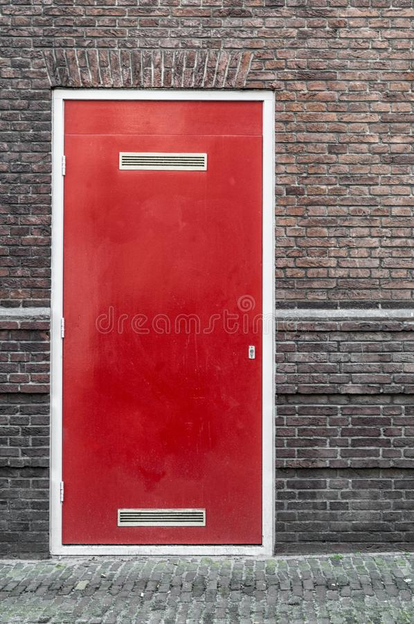 Une porte rouge incorporée dans un mur en pierre photos stock