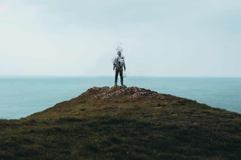 Une position à capuchon solitaire de figure sur une colline, regardant à travers l'océan photo stock