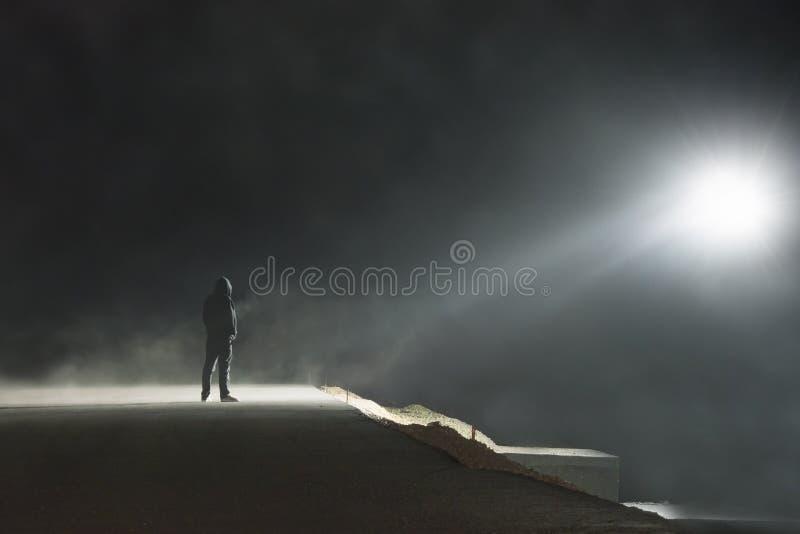 Une position à capuchon solitaire de figure sur une route brumeuse fantasmagorique la nuit regardant une lumière d'UFO dans le ci photo libre de droits
