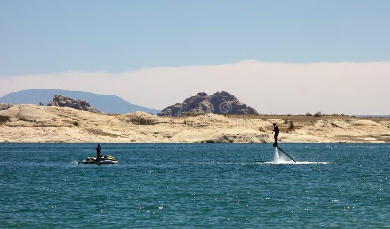 Une position d'homme sur des jets de l'eau à un réservoir dans le désert image libre de droits