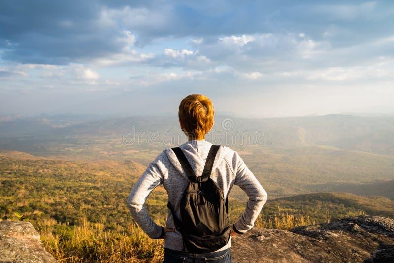 Une position de femme sur la montagne rocheuse regardant la vue naturelle scénique et le beau ciel bleu photographie stock