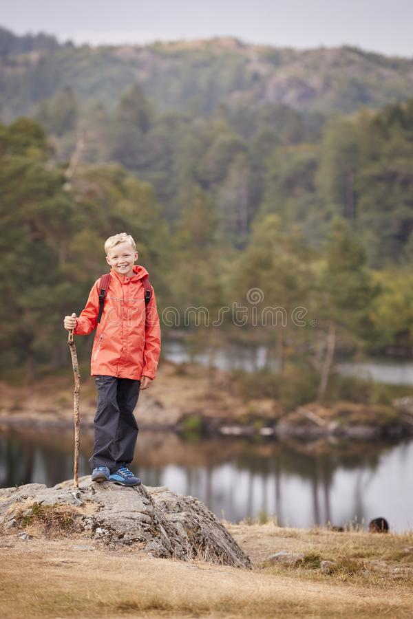 Une position de garçon sur une roche par un lac tenant un bâton, souriant à la caméra, secteur de lac, R-U, verticale image stock