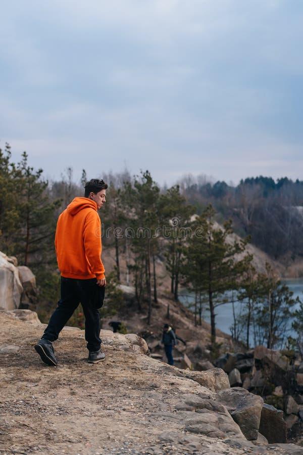 Une position de jeune homme au bord d'une falaise pose pour la cam?ra photographie stock libre de droits