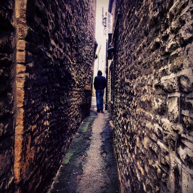 Une position de personne dans une voie étroite entre deux murs de briques photos libres de droits