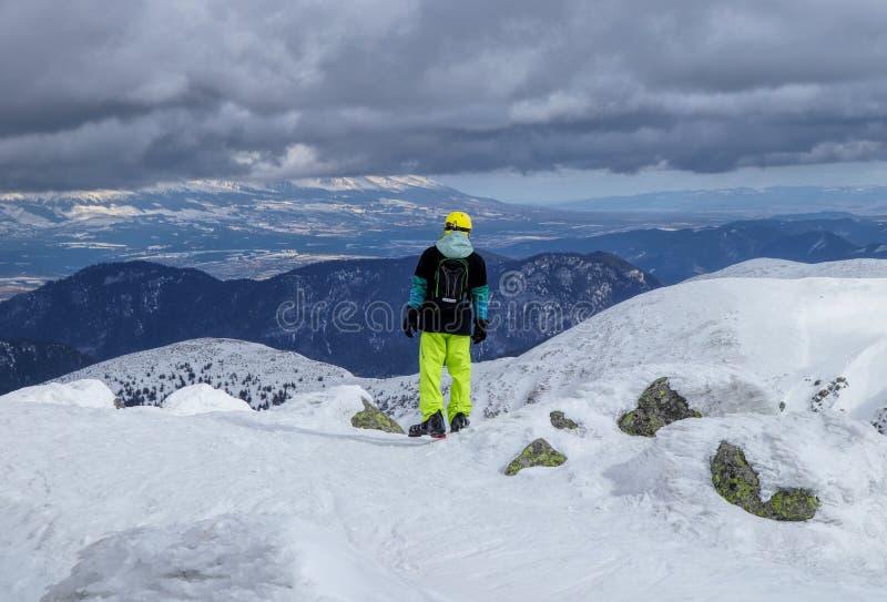 Une position de skieur d'homme au bord de montagne et regard vers le bas à la vallée et essayer de trouver le bon freeride Hauts  images stock