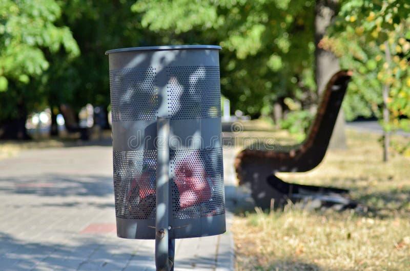Une poubelle noire dans la ville sur une allée près des arbres et des bancs photos libres de droits