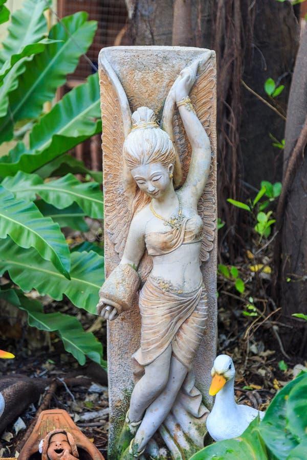 Une poupée féerique de statue et de canard avec des arbres dans le jardin image stock