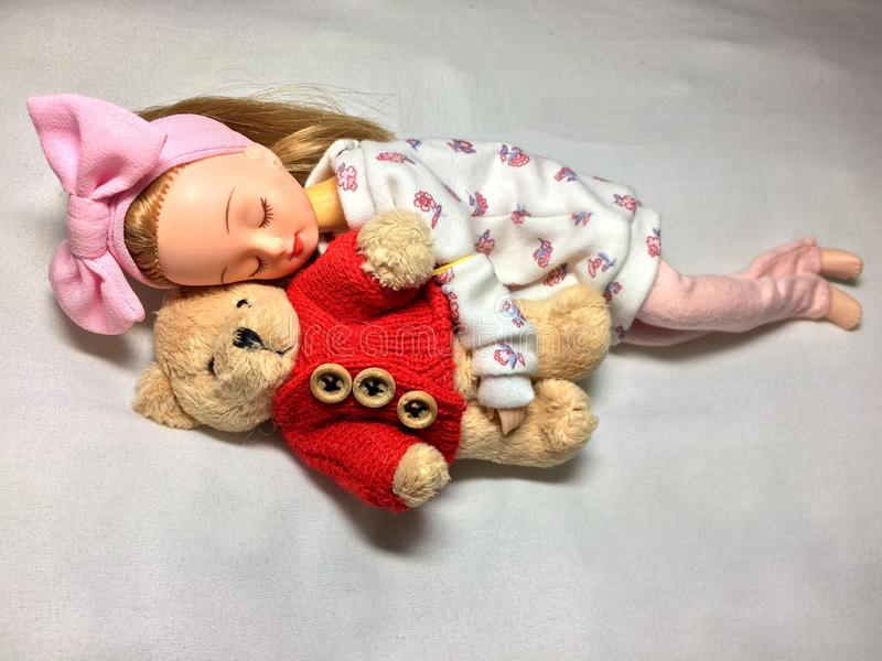 Une poupée japonaise adorable dort avec son ours de nounours photo stock
