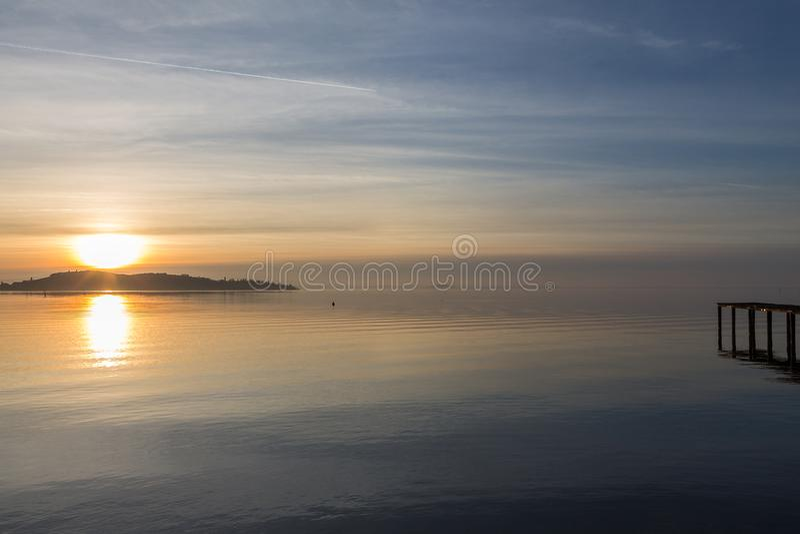 Une pousse d'un coucher du soleil au-dessus d'un lac, avec le soleil descendant derrière une île et un pilier du côté droit photos stock