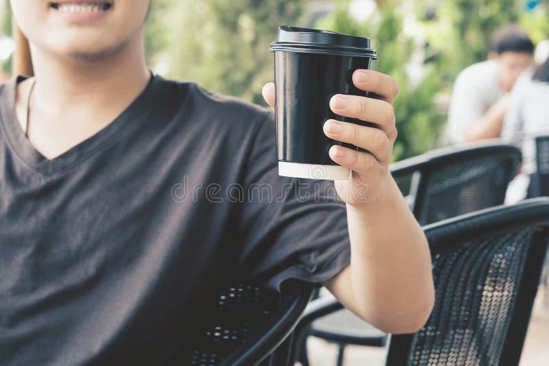 Une prise heureuse de visage de sourire d'homme par tasse de café d'emporter photo stock