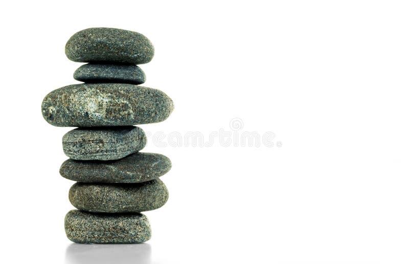 Une pyramide de sept pierres dans l'équilibre est isolée sur un blanc photo libre de droits