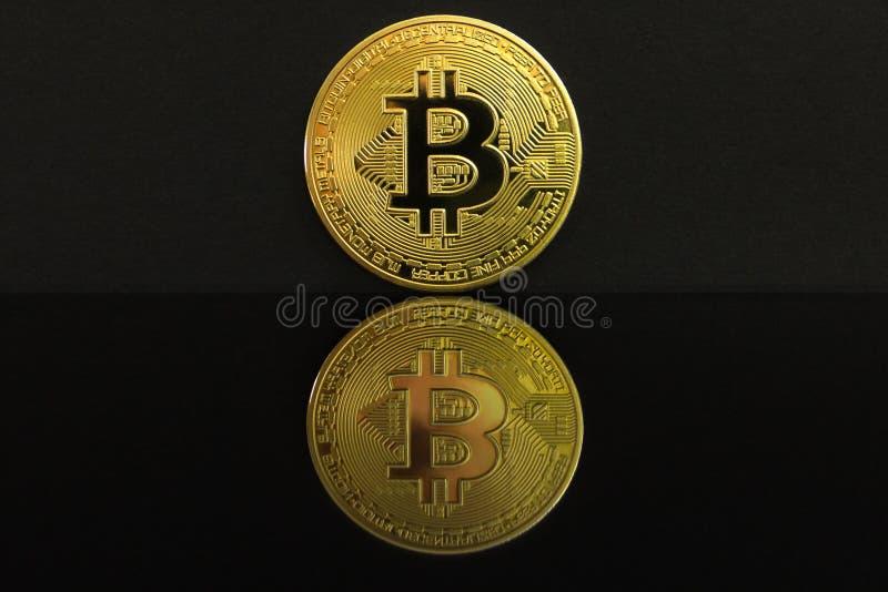 Une réflexion de miroir d'une grande pièce de monnaie d'or de BTC La pièce de monnaie du bitcoin est sur une table noire et un fo image stock
