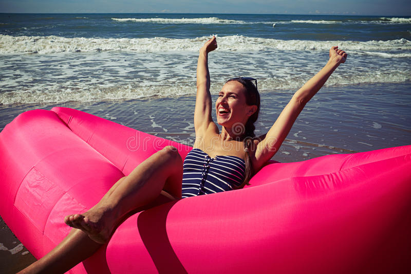 Une réjouissance femelle sur un canot en caoutchouc profond-attrayant d'air levant son Han photographie stock
