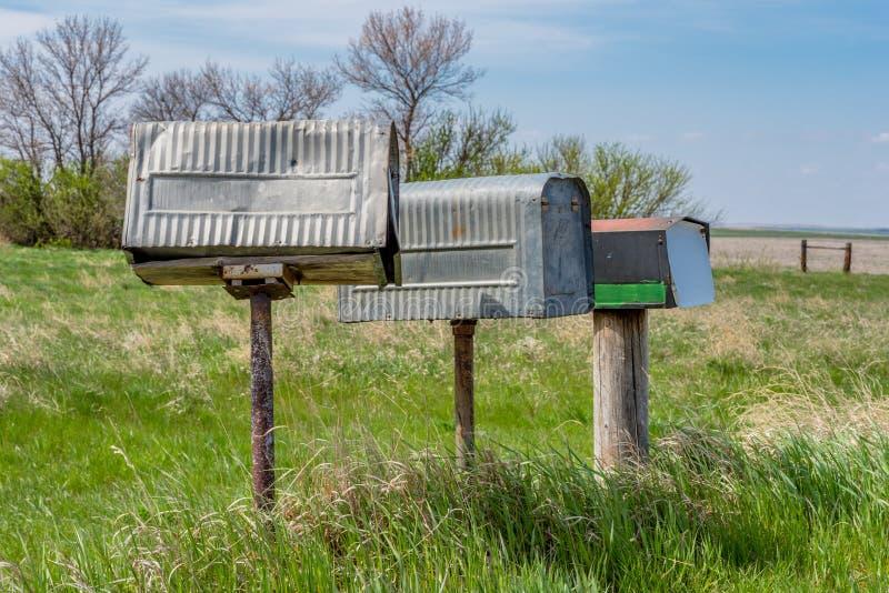 Une rangée de trois vieilles boîtes aux lettres d'agriculteurs en métal en Saskatchewan rurale, Canada photo stock
