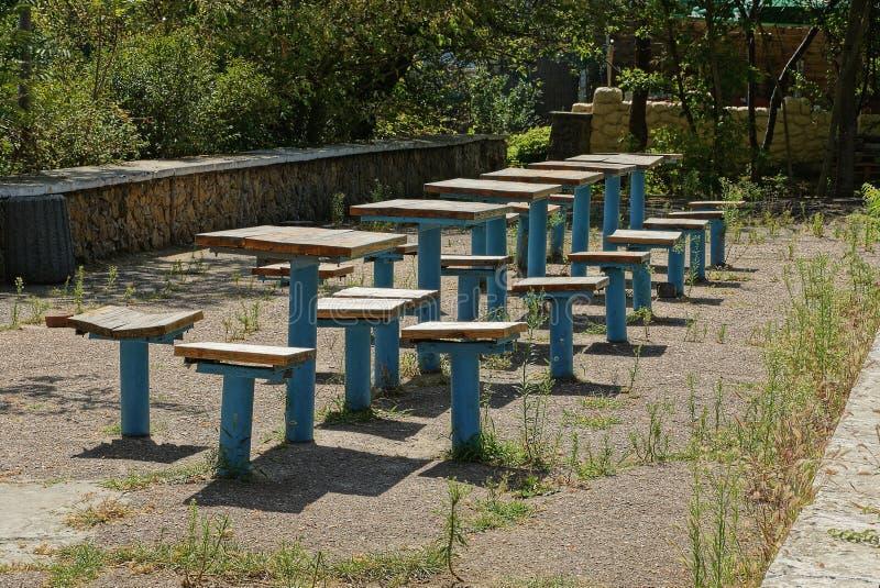 Une rangée de vieilles chaises et de tables expédient faites de fer et conseils sur l'asphalte dans l'herbe photos stock