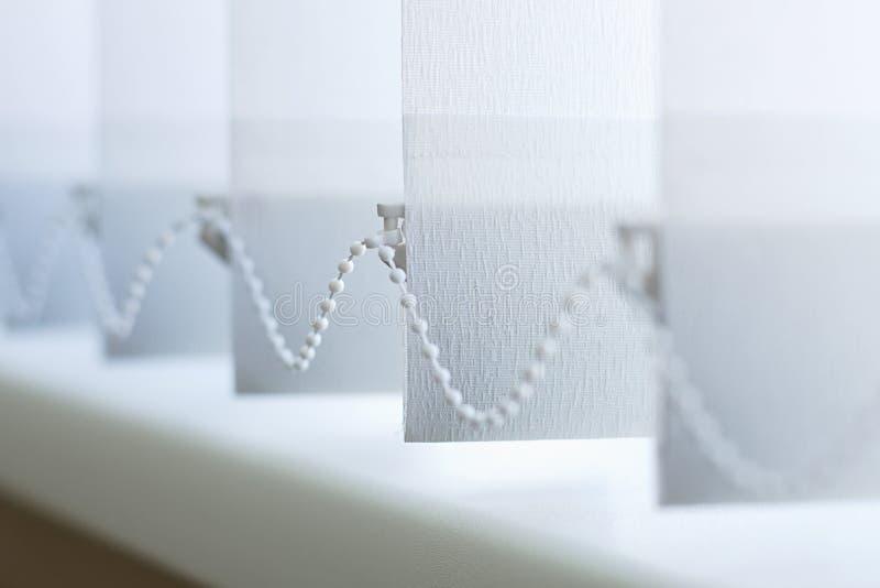 Une rangée des abat-jour verticaux blancs couvrent la lumière du soleil de la fenêtre Fin vers le haut photos libres de droits