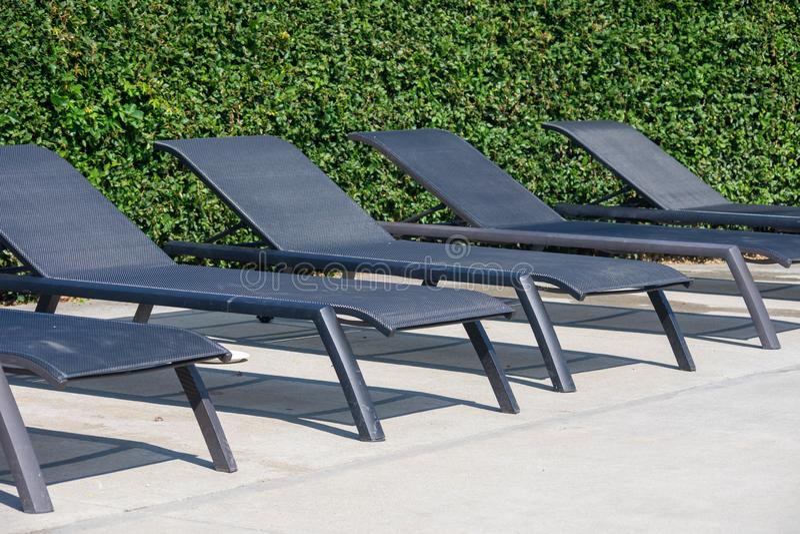 Une rangée des chaises vides de piscine pour se coucher avec un fond vert un jour ensoleillé photographie stock libre de droits