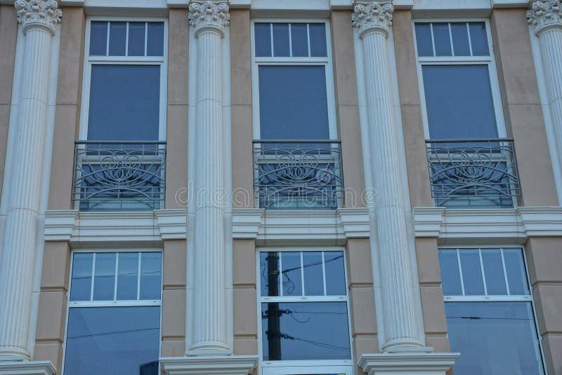 Une rangée des fenêtres sur un mur brun avec les colonnes grises image libre de droits