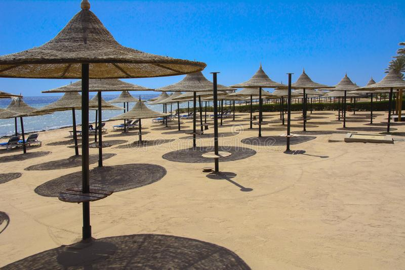 Une rangée des parapluies de paille à protéger contre la surchauffe et les lits pliants sur une plage sablonneuse contre un ciel  image libre de droits
