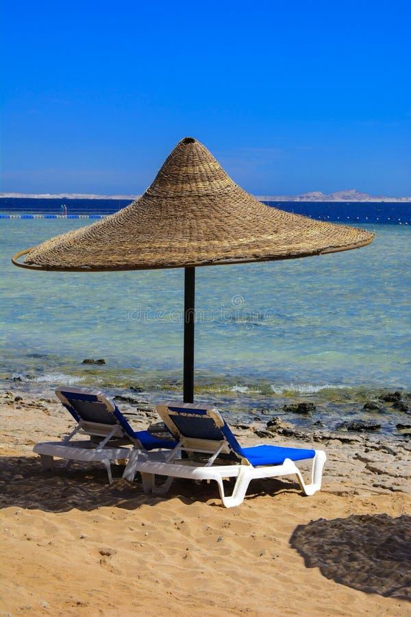 Une rangée des parapluies de paille à protéger contre la surchauffe et les lits pliants sur une plage sablonneuse contre un ciel  photo stock