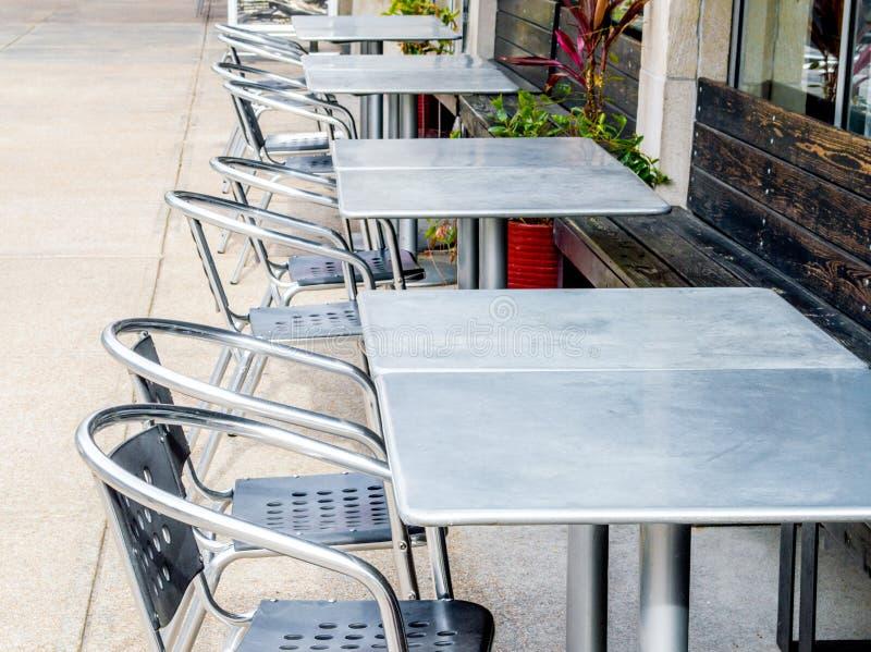 Une rangée des tables et des chaises vides en métal dehors photographie stock