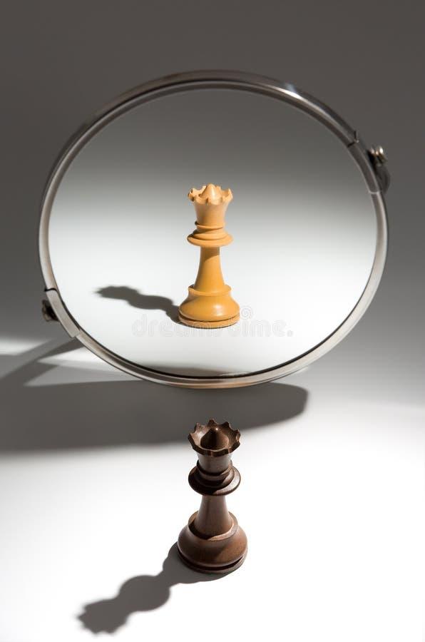 Une reine noire regarde dans un miroir pour se voir en tant que reine blanche photos stock