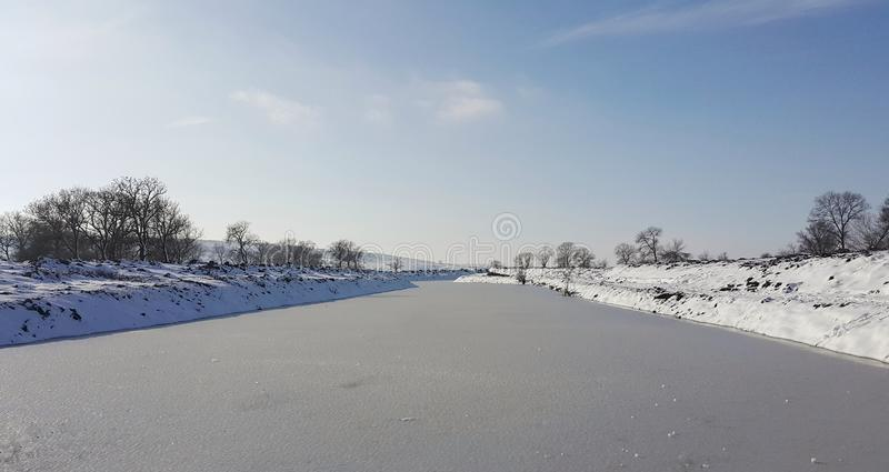 Une rivière congelée en captivité près du froid Neige et ciel bleu avec les nuages et le bâton J'aime marcher sur une rivière con images stock