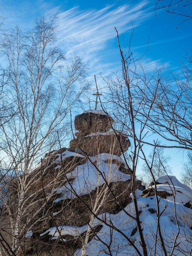 Une roche avec une croix orthodoxe sur l'église de montagne pendant l'hiver dans Belokurikha, Russie photo libre de droits