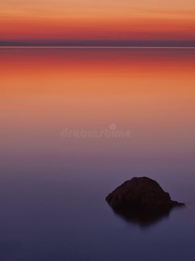 Une roche en mer au coucher du soleil photographie stock libre de droits