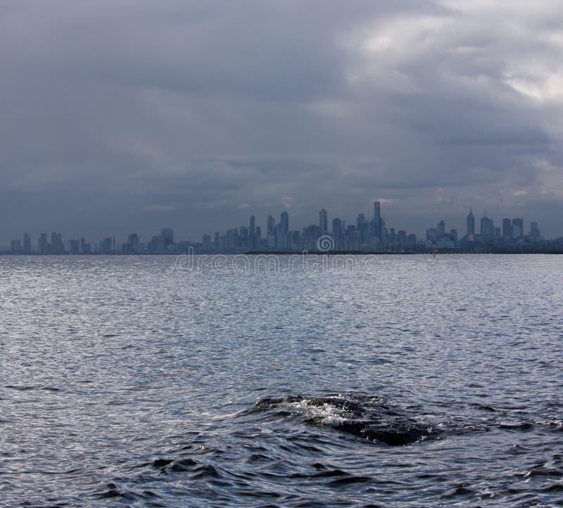 Une roche en mer et l'horizon de Melbourne à l'arrière-plan photo libre de droits