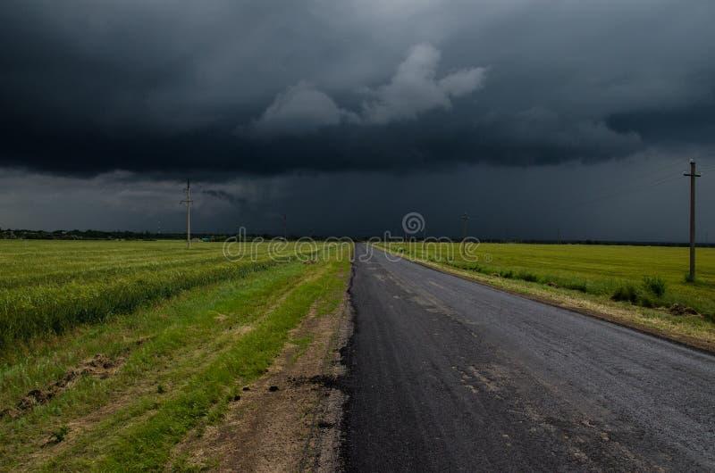 une route goudronnée dans un domaine vert devant un orage fort photos stock