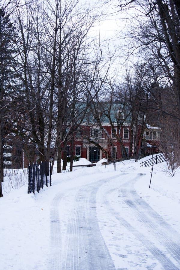 Une route neigeuse et glaciale, menant à une maison rouge entre les arbres image stock