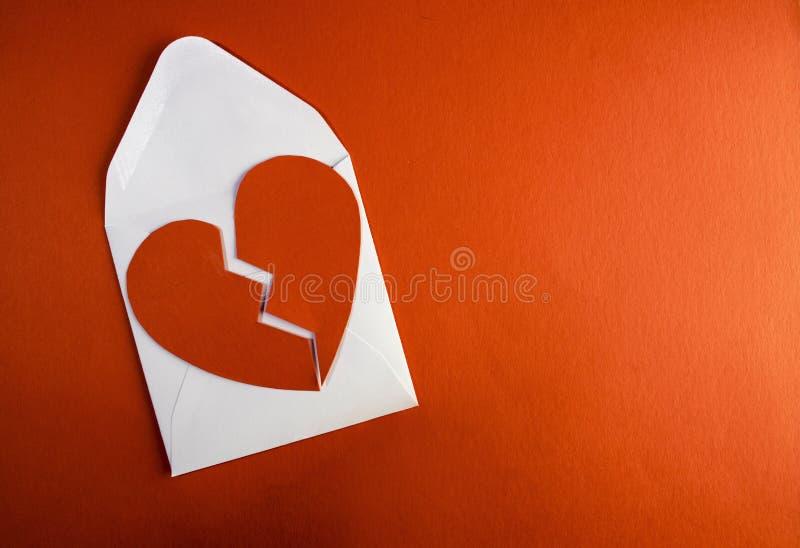 Une rupture vers le haut de lettre d'enveloppe avec un cassé a déchiré le coeur de papier photographie stock