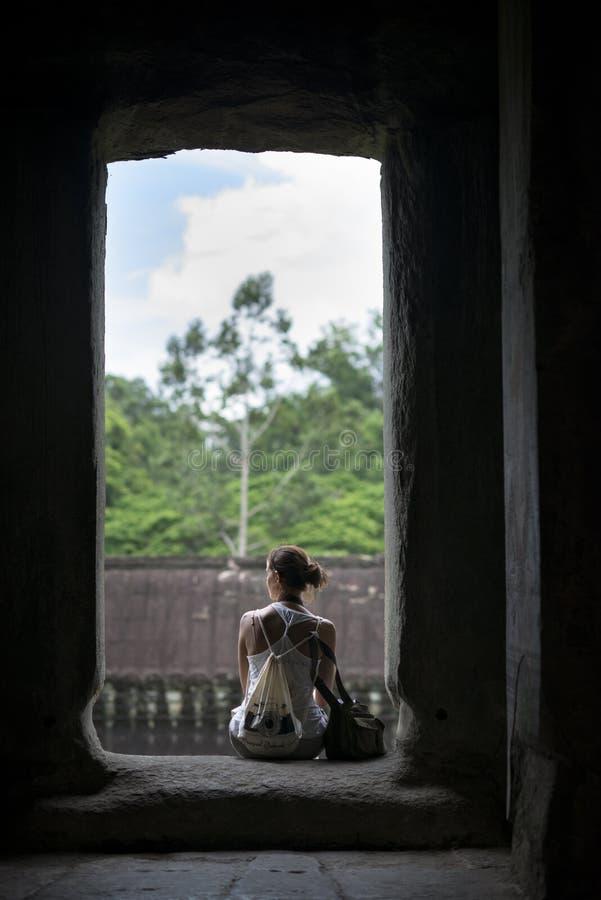 Une séance de touristes se reposant dans les ruines au temple d'Angkor Vat, Siem Reap, Cambodge photographie stock