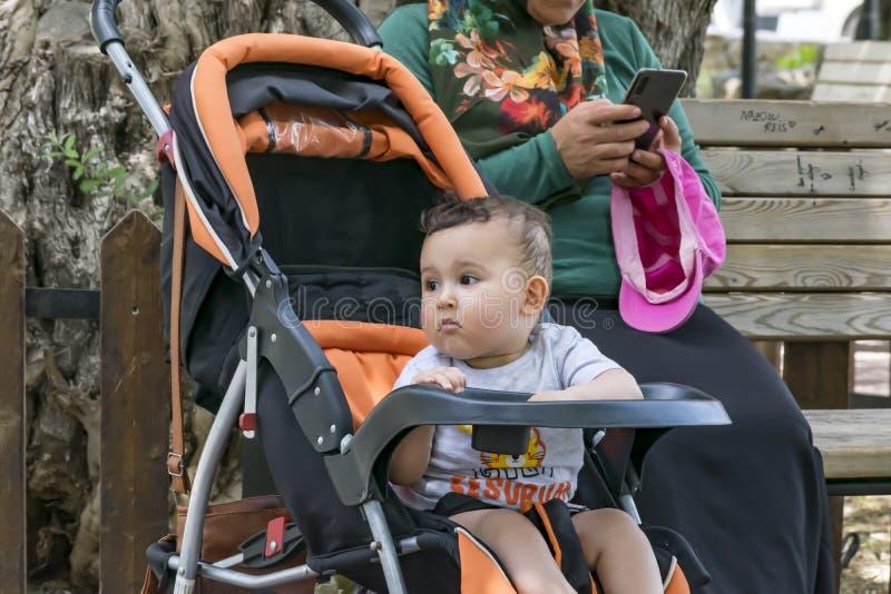 Une séance ennuyée par enfant dans la poussette de bébé Sa mère habillée dans l'habillement musulman traditionnel utilisant un sm photographie stock libre de droits