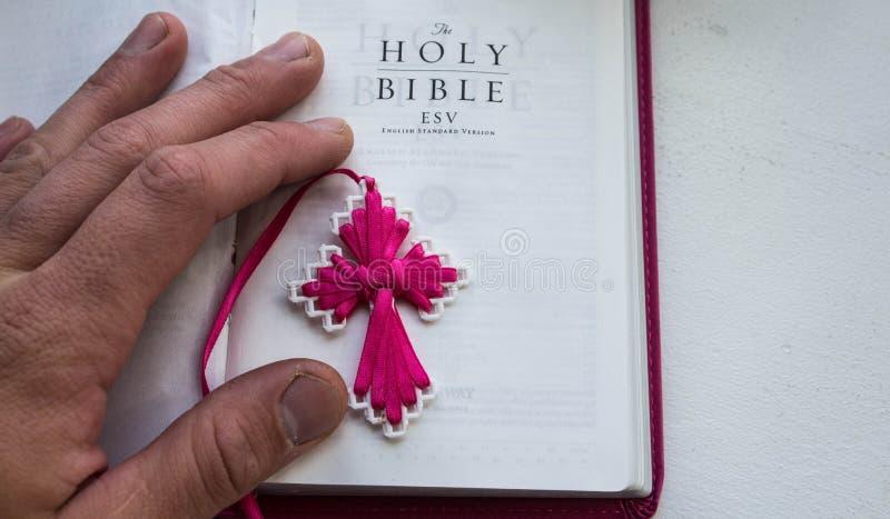 Une Sainte Bible ouverte avec une main de croix et d'homme sur un fond blanc image stock