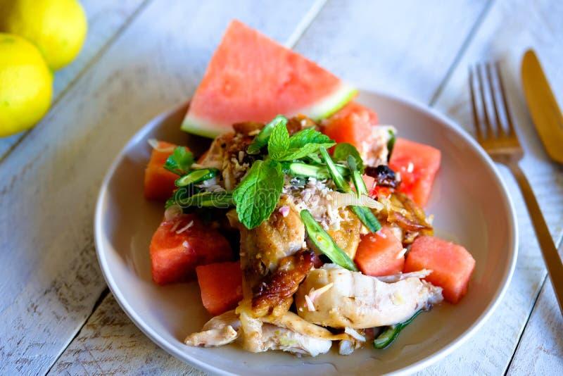 Une salade d'été faite à partir de la pastèque fraîche et des herbes fraîches avec la cuisse grillée de poulet photos stock
