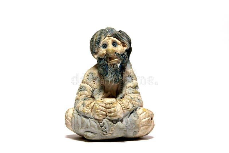 Une sculpture en pierre d'un homme s'asseyant d'isolement image libre de droits