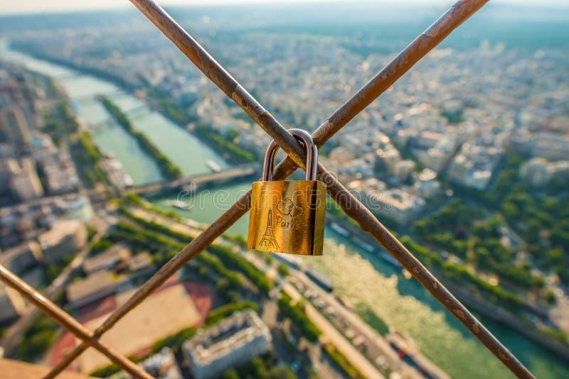 Une serrure d'or placée sur une barrière de Tour Eiffel regardant au-dessus de la rivière la Seine photo stock