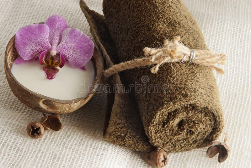 Une serviette pliée et une orchidée fleurissent en lait dans une noix de coco sur une serviette tissée légère, préparation pour l photos libres de droits