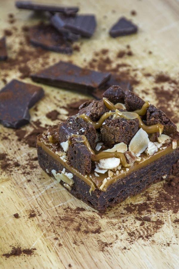 Une seule pièce de 'brownie' avec du chocolat et le cacao sur le fond en bois photographie stock