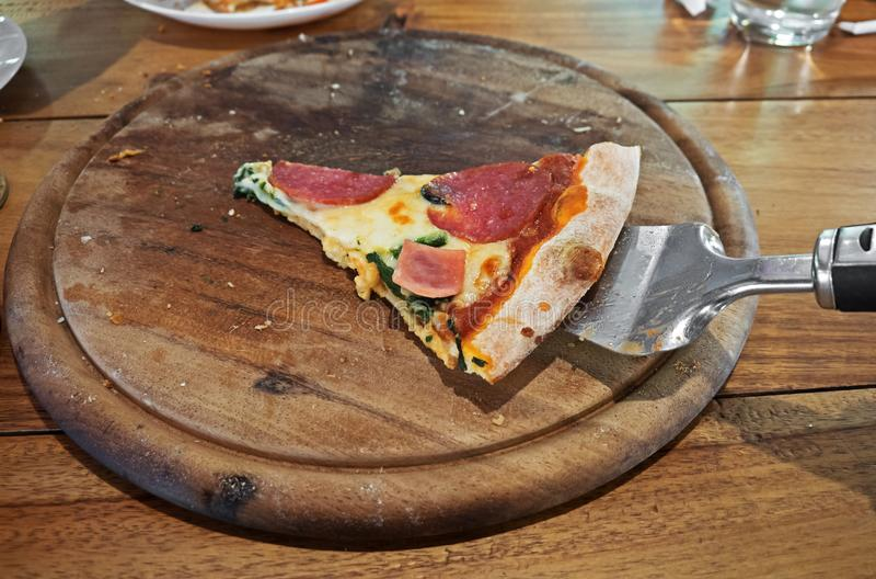Une seule pièce de pizza laissé sur le plateau en bois photos stock